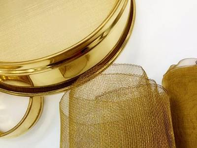 Two brass mesh test sieves and two rolls of brass woven mesh on the white background.