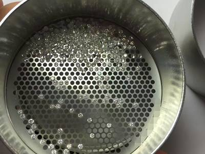 Some diamonds in the stainless steel calibrated test sieve.