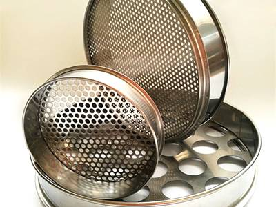 Three perforated grading sieves in round holes and different diameters on the white background.