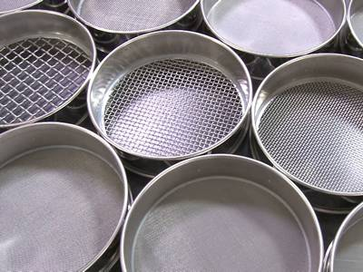 Eleven different sizes and openings mid point test sieves on the table.