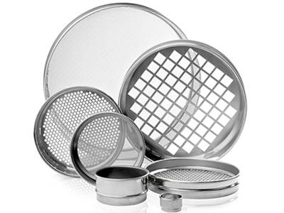 Seven perforated plate sieves on the white background with different diameters and opening.
